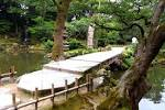 a stone bridge leads you to kaiseki pagoda allowing visitors to get a feel for a japanese garden